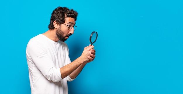 虫眼鏡で探して見つけようとしている若い狂ったひげを生やした男