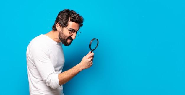 Молодой сумасшедший бородатый мужчина ищет и пытается найти с увеличительным стеклом