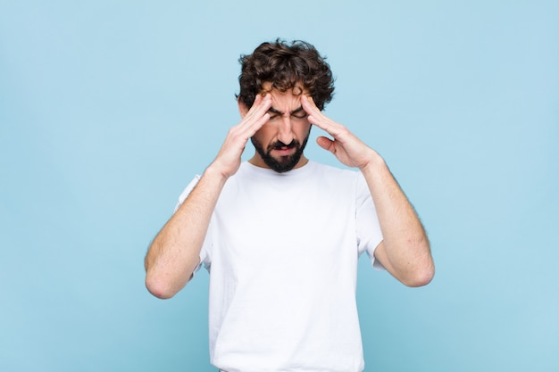 Young crazy bearded man looking stressed and frustrated, working under pressure with a headache and troubled with problems against wall