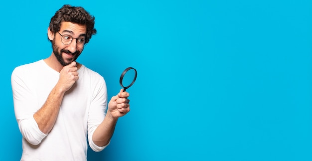 Young crazy bearded man looking and trying to find with a magnifying glass