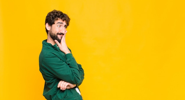 Young crazy bearded man on orange wall copy space.