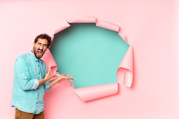Young crazy bearded man. paper hole