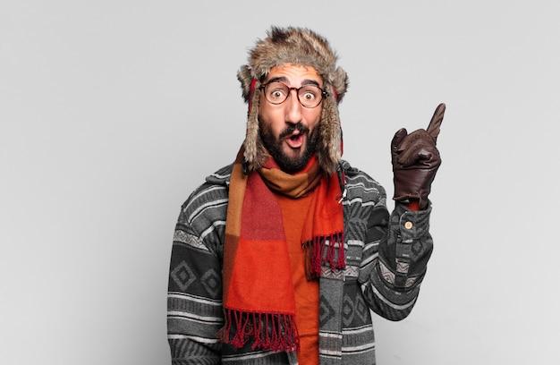 젊은 미친 수염된 남자. 가리키는 제스처. 승자처럼 승리를 축하하고 겨울 옷을 입고