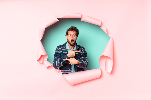 Young crazy bearded man. pointing gesture. confused or doubting expression. paper hole empty background concept