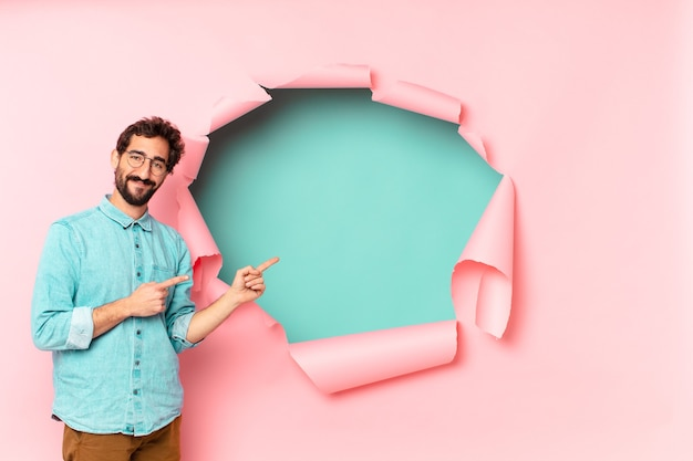 Young crazy bearded man. pointing gesture. paper hole empty background concept