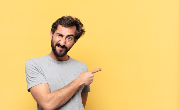若い狂ったひげを生やした男が横を指しているか、見せている