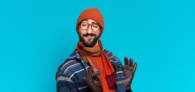 狂ったひげを生やした若い男の誇らしげな表情と冬の服を着ている