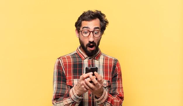 クレイジーなひげを生やした若い男が怖がった表情と電話を持っている