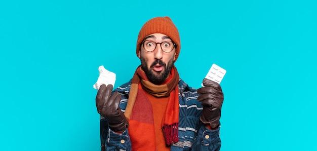 턱수염을 기른 젊은 남자는 충격을 받거나 놀란 표정을 짓고 겨울 옷을 입고 질병 개념을