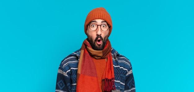 젊은 미친 수염된 남자. 충격을 받거나 놀란 표정과 겨울 옷을 입고