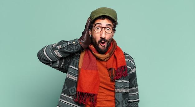 젊은 미친 수염 남자. 충격을 받거나 놀란 표정과 겨울 옷을 입고