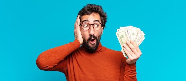 젊은 미친 수염된 남자. 충격을 받거나 놀란 표정. 달러 지폐 개념