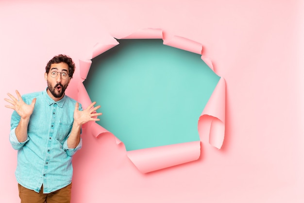 Young crazy bearded man. shocked or surprised expression. paper hole empty background concept