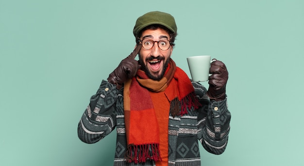 Young crazy bearded man. shocked or surprised expression and wearing winter clothes