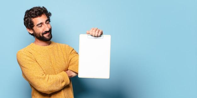 Молодой сумасшедший бородатый мужчина показывает лист бумаги с копией пространства