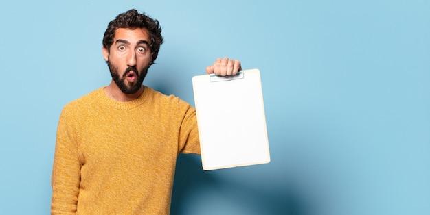 コピースペースで一枚の紙を示す若い狂ったひげを生やした男
