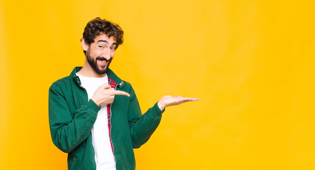 Young crazy bearded man smiling cheerfully and pointing to copy space on palm on the side, showing or advertising an object against flat wall