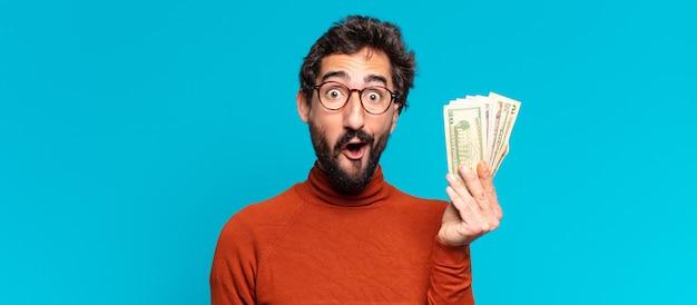 젊은 미친 수염된 남자 놀란 표정. 달러 지폐 개념