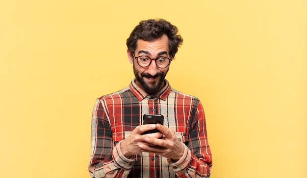 Young crazy bearded man surprised expression and holding a phone