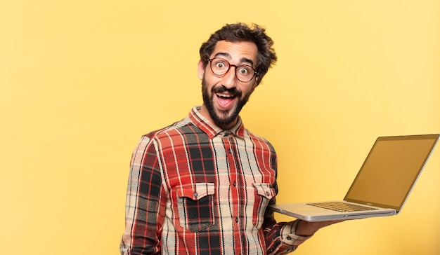 Young crazy bearded man surprised expression and a laptop