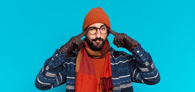 젊은 미친 수염된 남자. 생각하거나 의심하는 표정과 겨울 옷