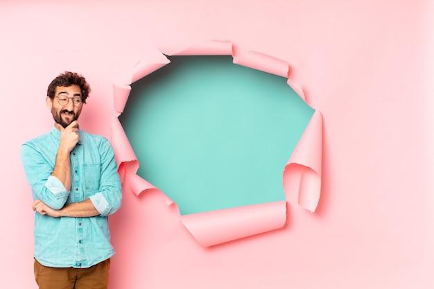 Молодой сумасшедший бородатый мужчина. думающее или сомневающееся выражение. бумажная дыра пустой фон концепция
