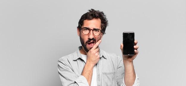 젊은 미친 수염된 남자. 생각하거나 의심하는 표현. 전화 화면 개념