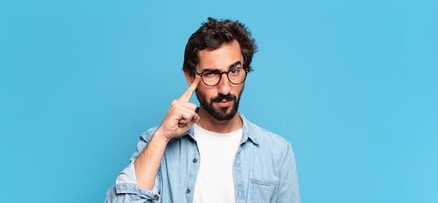 Молодой сумасшедший бородатый мужчина. мышление или сомневающееся выражение