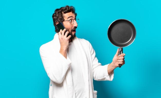 鍋で調理するバスローブを着た若い狂ったひげを生やした男
