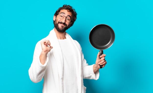 Молодой сумасшедший бородатый мужчина в халате готовит на сковороде