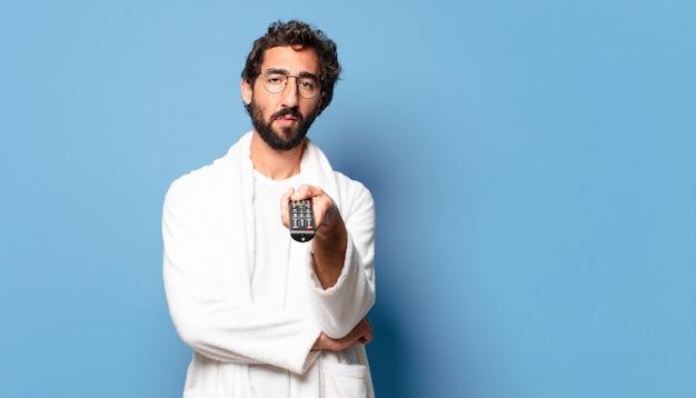 Молодой сумасшедший бородатый мужчина в халате с пультом дистанционного управления