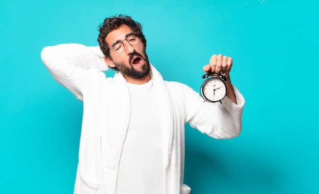 Young crazy bearded man wearing bathrobe and an alarm clock