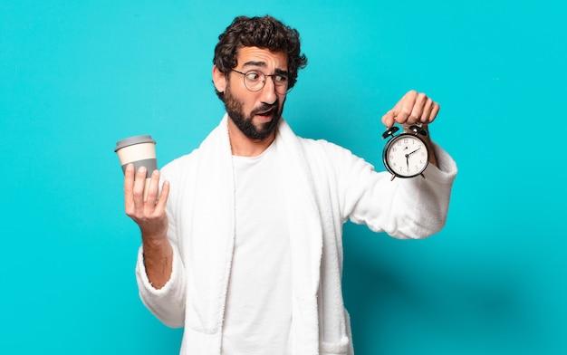 Молодой сумасшедший бородатый мужчина в халате и будильнике