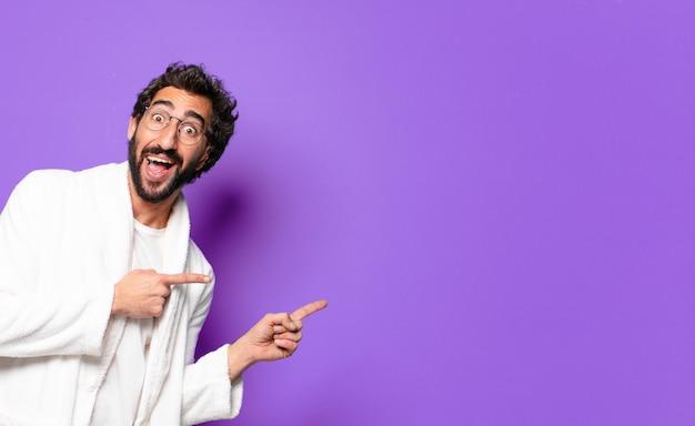 Молодой сумасшедший бородатый мужчина в халате и просыпается дома