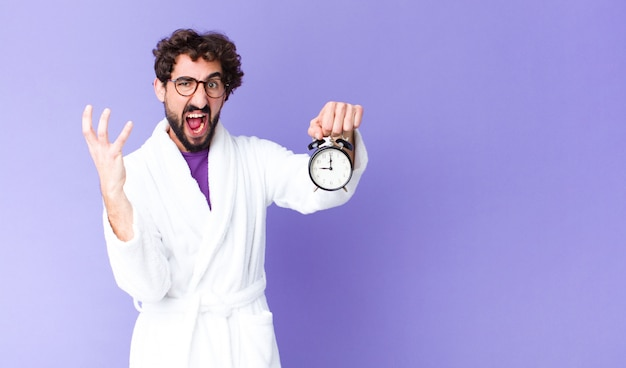 Young crazy bearded man  wearing bathrobe holding an alarm clock