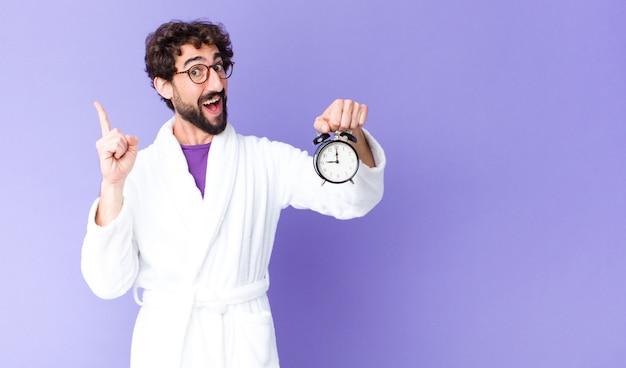 Молодой сумасшедший бородатый мужчина в халате с будильником
