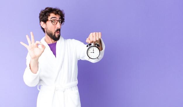 目覚まし時計を保持しているバスローブを着ている若いクレイジーひげを生やした男