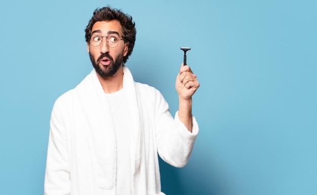 Молодой сумасшедший бородатый мужчина в халате. концепция бритья