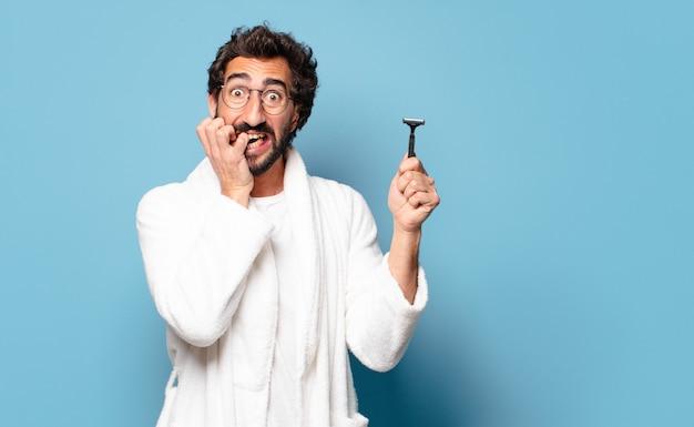 목욕 가운을 입고 젊은 미친 수염 된 남자. 면도 개념