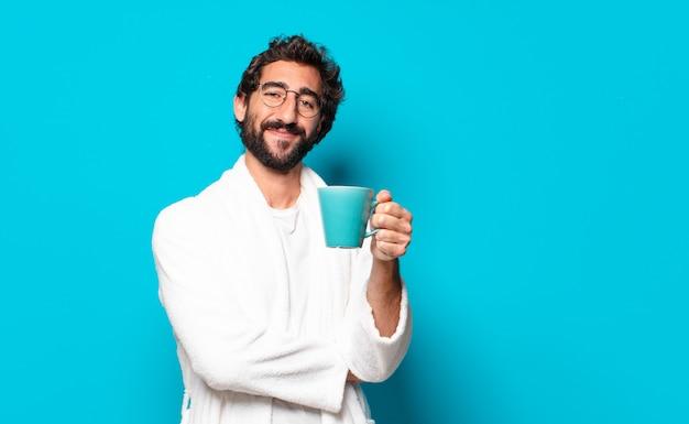 Молодой сумасшедший бородатый мужчина в халате с чашкой кофе