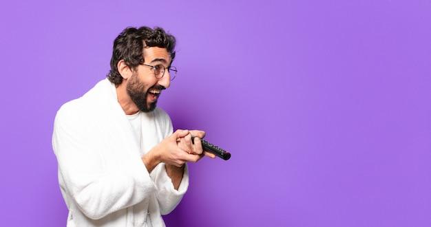 Молодой сумасшедший бородатый мужчина в халате с пультом дистанционного управления от телевизора