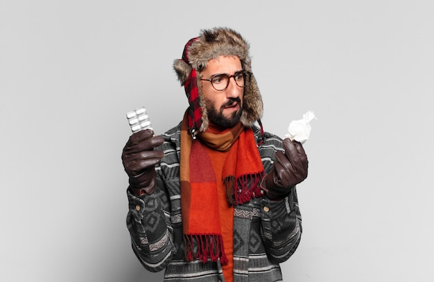 Young crazy bearded man and wearing winter clothes illness concept