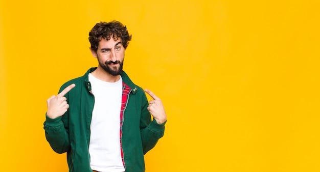 Молодой сумасшедший бородатый мужчина с плохим поведением выглядит гордым и агрессивным, указывая вверх или весело жестикулируя руками у плоской стены Premium Фотографии