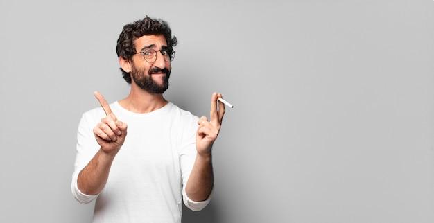 담배와 젊은 미친 수염 된 남자. 금연 개념이 없습니다.
