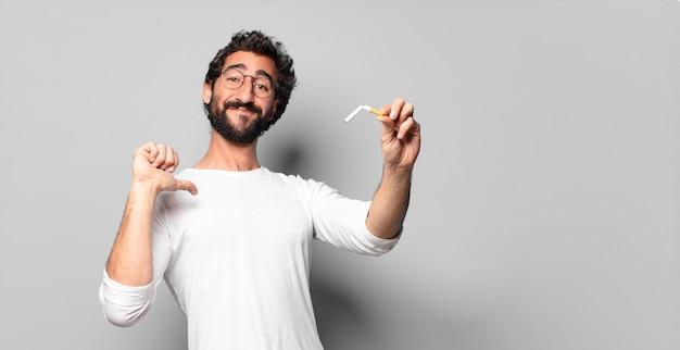 Молодой сумасшедший бородатый мужчина с сигаретой. концепция не курить.