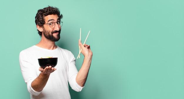Молодой сумасшедший бородатый мужчина с миской рамэн с лапшой