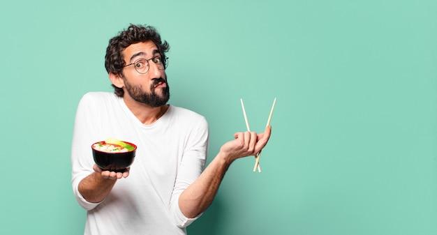 麺ラーメン丼を持つ若い狂ったひげを生やした男