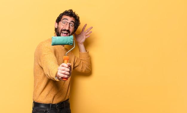 페인트 롤러 페인팅 및 벽 색상 변경 젊은 미친 수염 난 남자