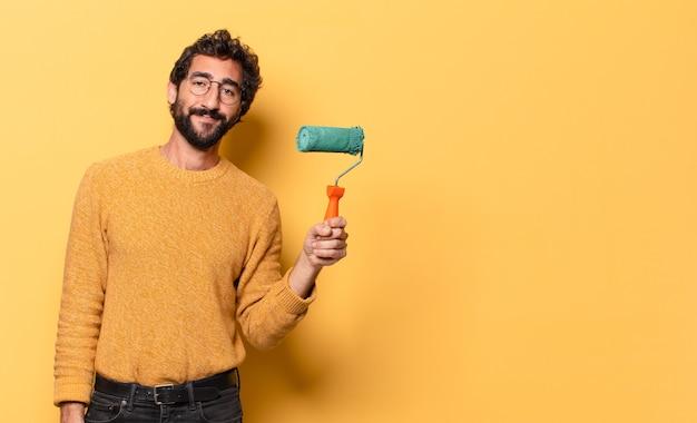 Молодой сумасшедший бородатый мужчина с малярным валиком рисует и меняет цвет стены