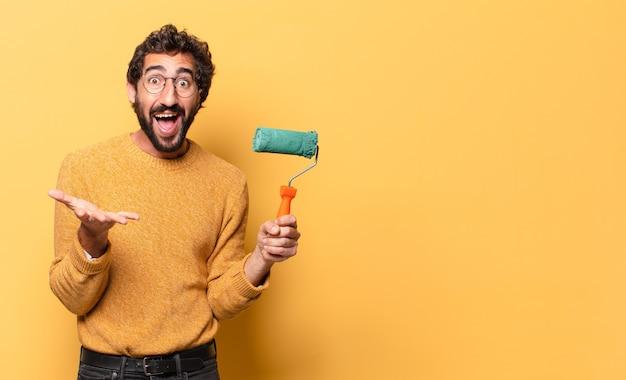 Молодой сумасшедший бородатый мужчина с малярным валиком рисует и меняет цвет стен